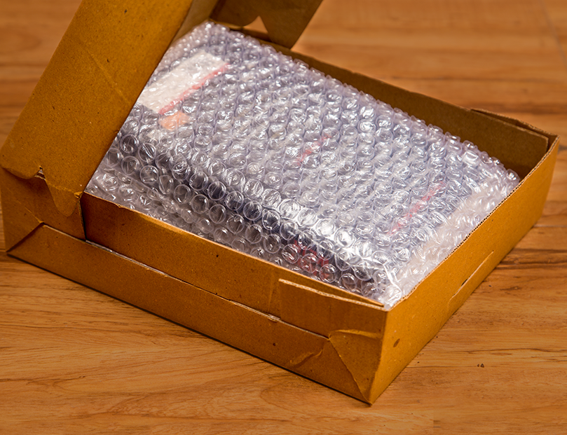 Book wrapped in bubble wrap with a corrugated box
