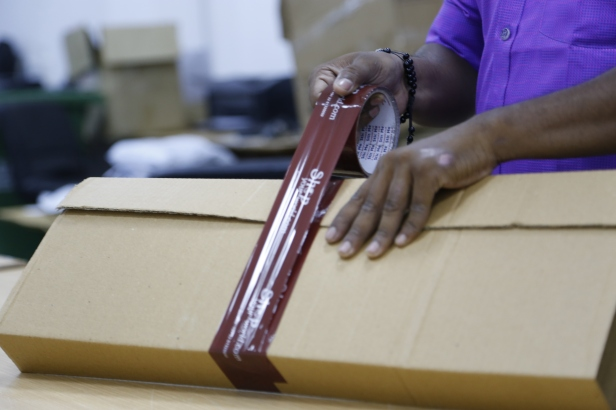 maroon tape being applied on corrugated box brown by a person