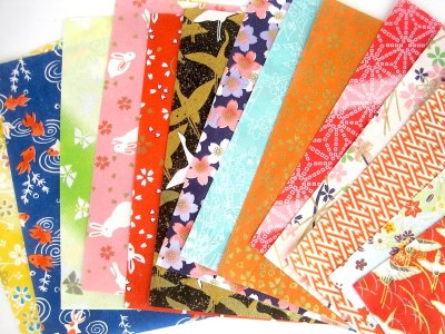 fourteen different prints of origami paper in different colors on white background