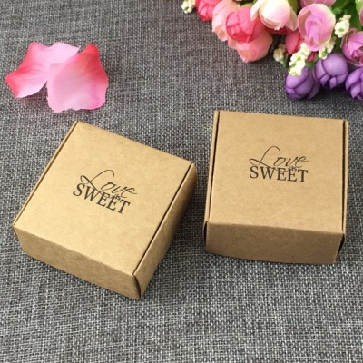 two brown sweet boxes with black text love sweet on grey textile background with blue and purple flowers on top right