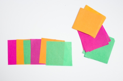 arranged green pink and orange tissue paper in squares on white background